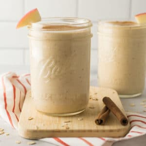 healthy apple pie smoothie on wood board with oats and cinnamon sticks