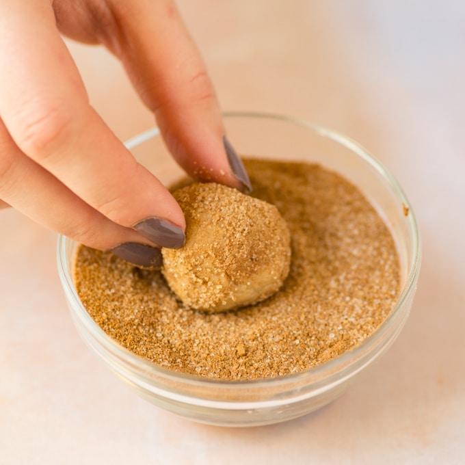hand dipping snickerdoodle cookie dough into cinnamon sugar