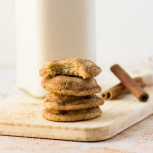 stack of chai snickerdoodle cookies with cinnamon sticks and glass of milk