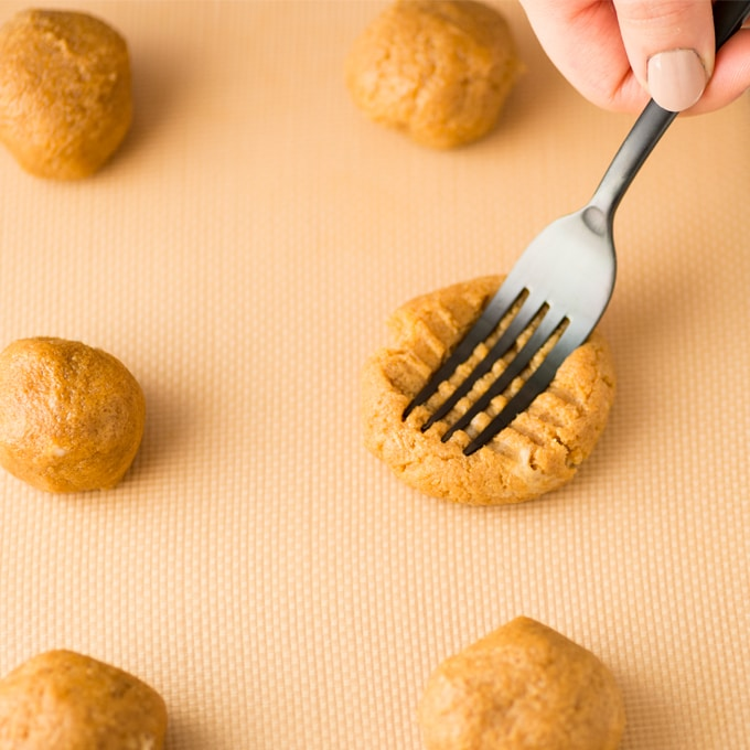 hand pressing fork into vegan and gluten free peanut butter cookie