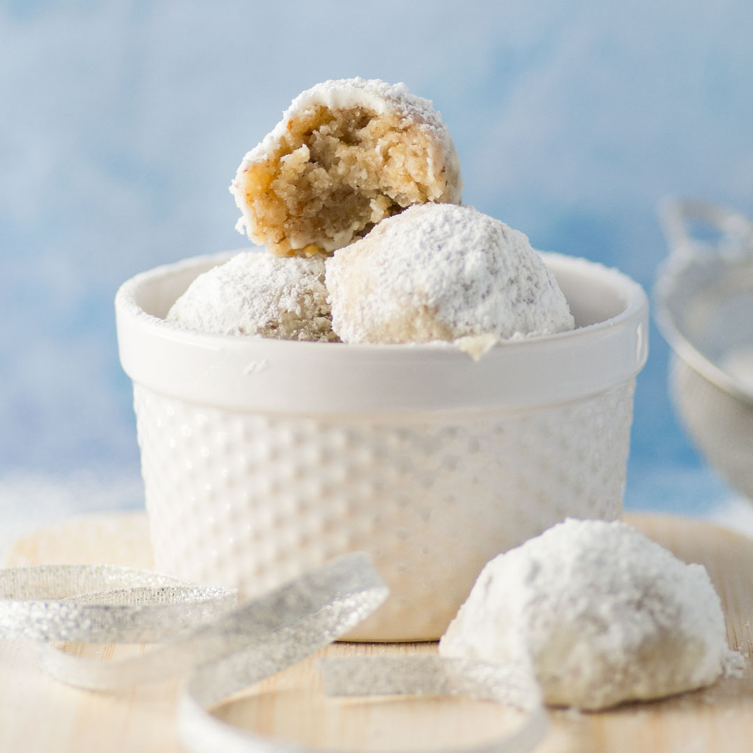 vegan russian tea cakes in white dish on blue background