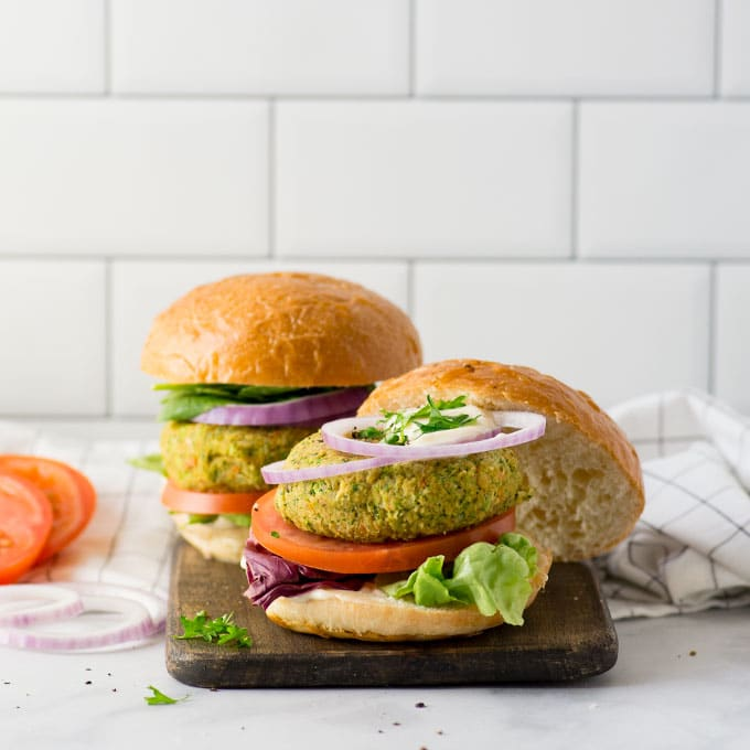 veggie burger with lettuce, tomato, red onion, mayo on bun with white background