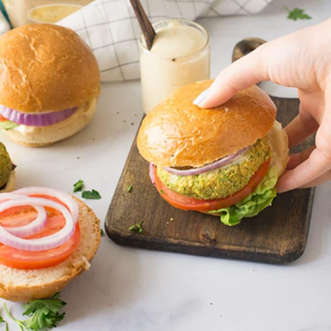 hand grabbing veggie burger on wood board