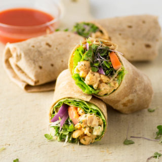 vegan buffalo chickpea salad wrap on wood board with hot sauce