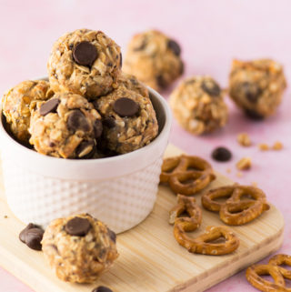 chocolate chip peanut butter energy bites with pretzels on pink background