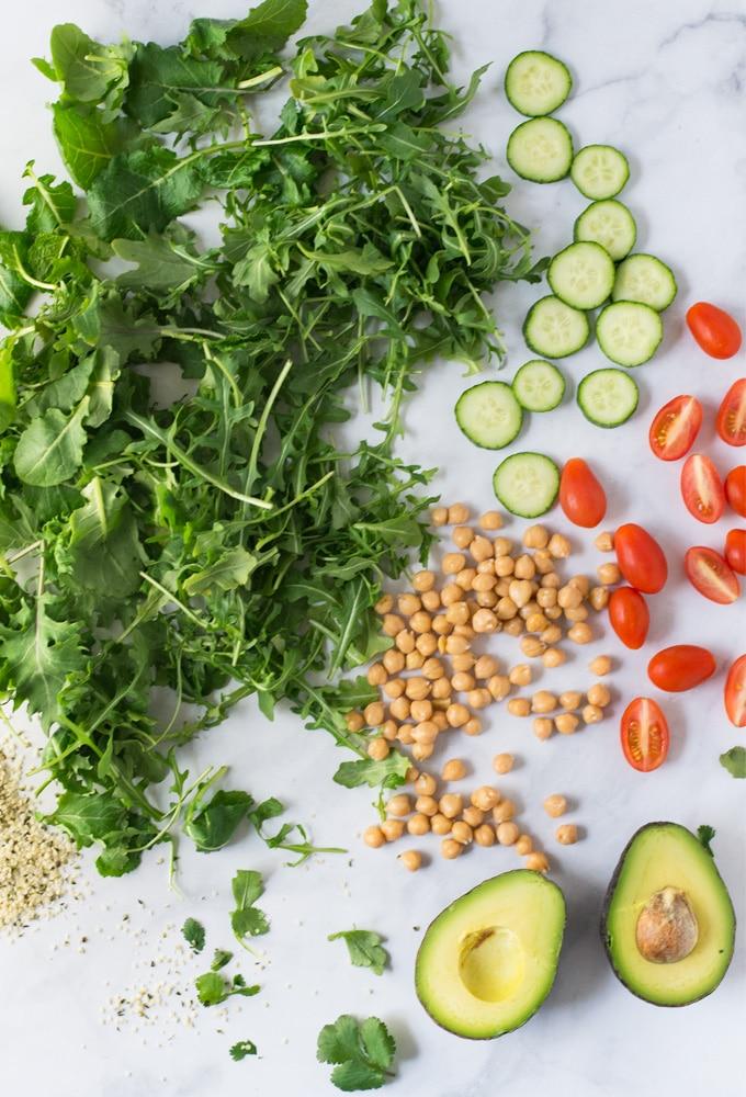 arugula, kale, cucumbers, tomatoes, avocado, chickpeas, hemp seeds on marble background