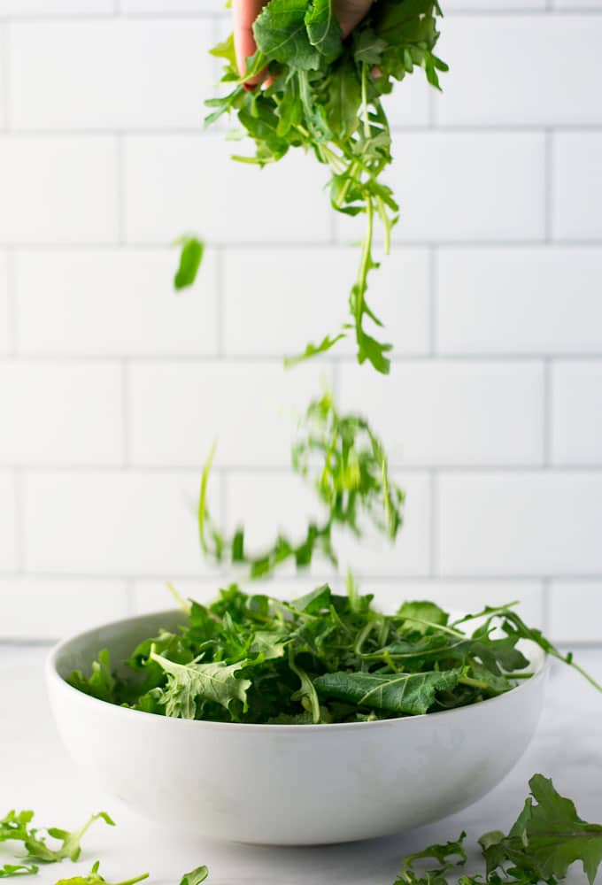 hand pouring lettuce into bowl