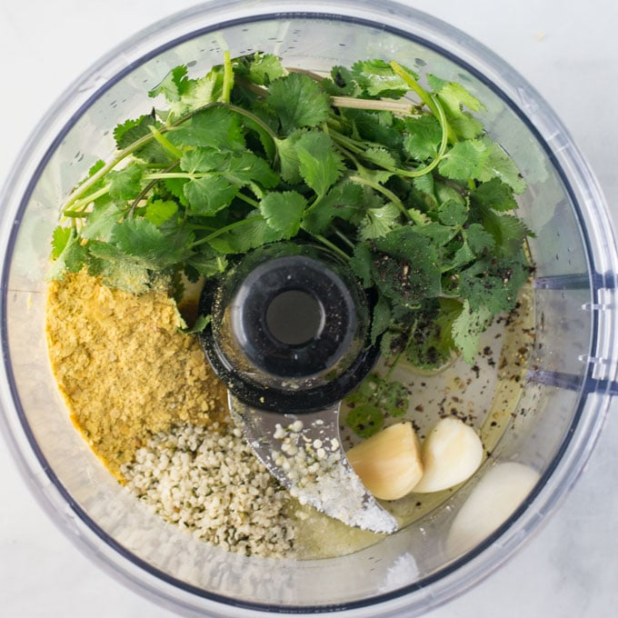 ingredients for vegan salad dressing in food processor. Cilantro, nutritional yeast, hemp seeds, and garlic
