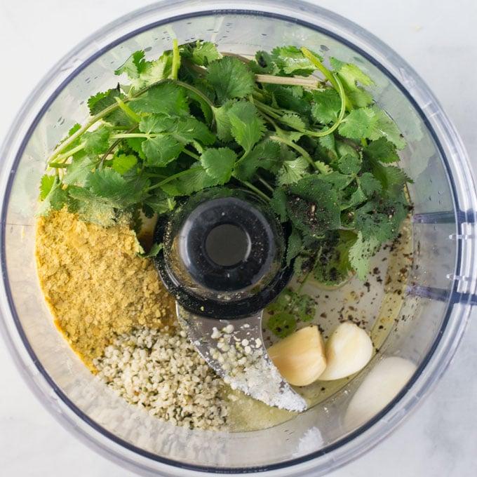 ingredients for vegan salad dressing in food processor. Cilantro, nutritional yeast, hemp seeds, and garlic