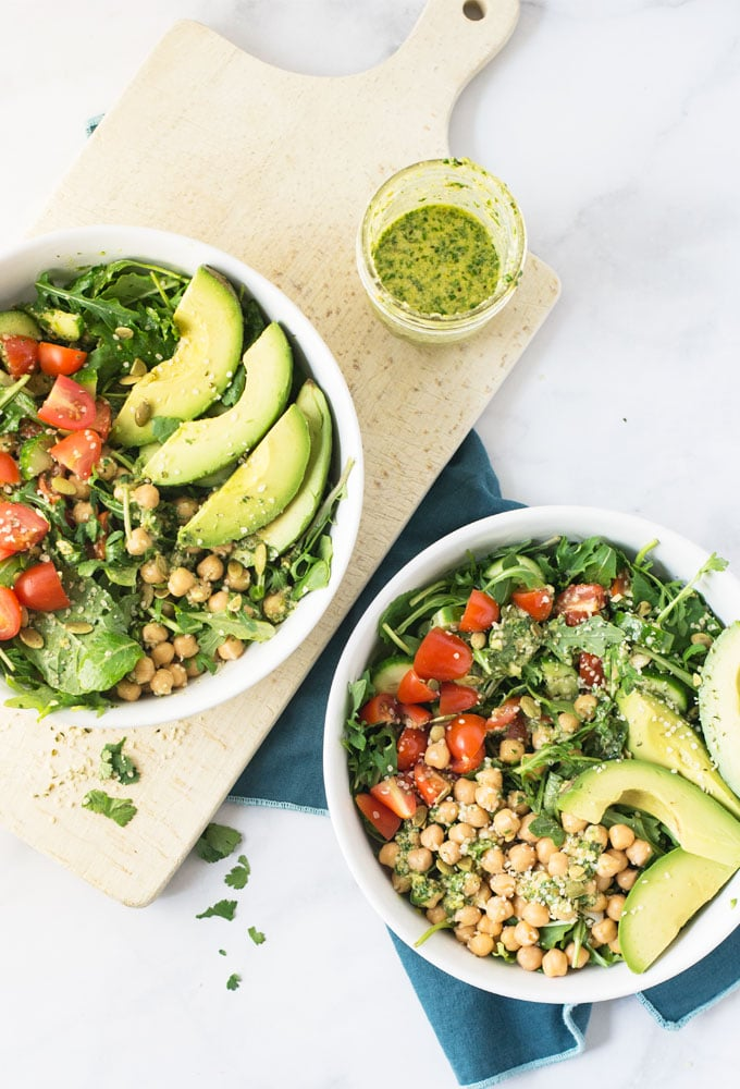 two vegan salads with chickpeas, tomatoes, avocado in white bowls with homemade dressing
