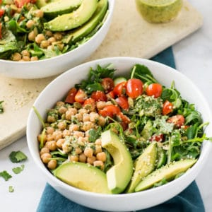 vegan salad with chickpeas, tomatoes, and avocado in white bowl
