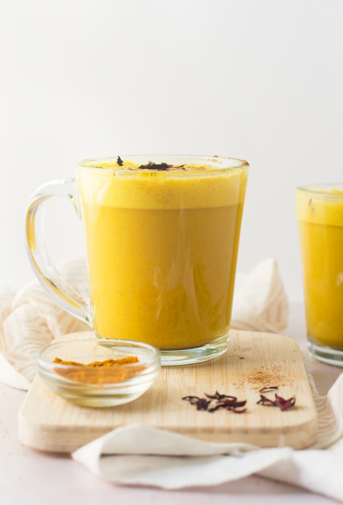 turmeric latte in glass mug with rose petals