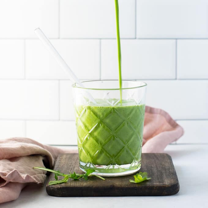 pouring green smoothie into glass with glass straw