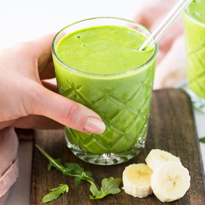 hand grabbing green smoothie with banana slices and spinach