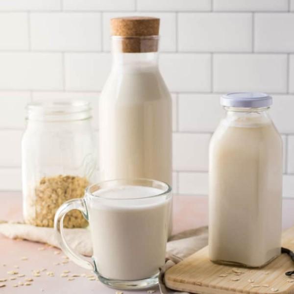 homemade oat milk on pink background