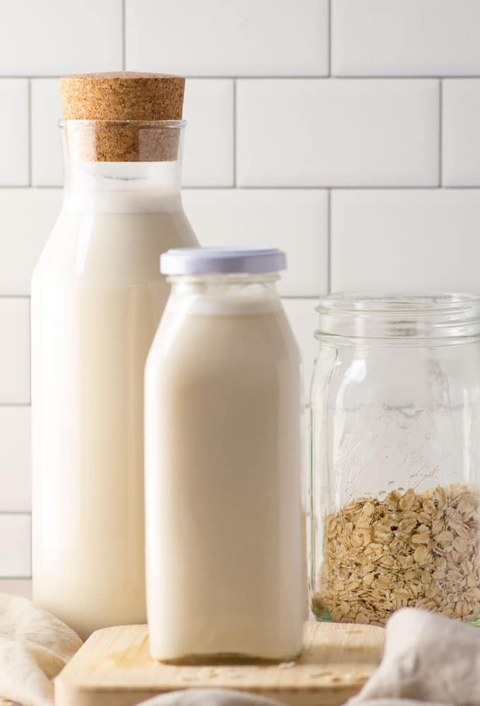 homemade oat milk in glass container with mason jar of rolled oats