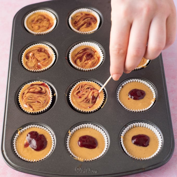 hand swirling jelly in peanut butter cups in mini cupcake tin.