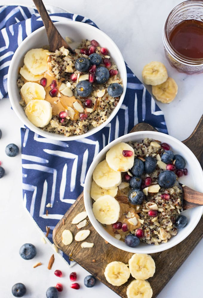 two bowls of vegan quinoa porridge with bananas, blueberries, and pomegranate