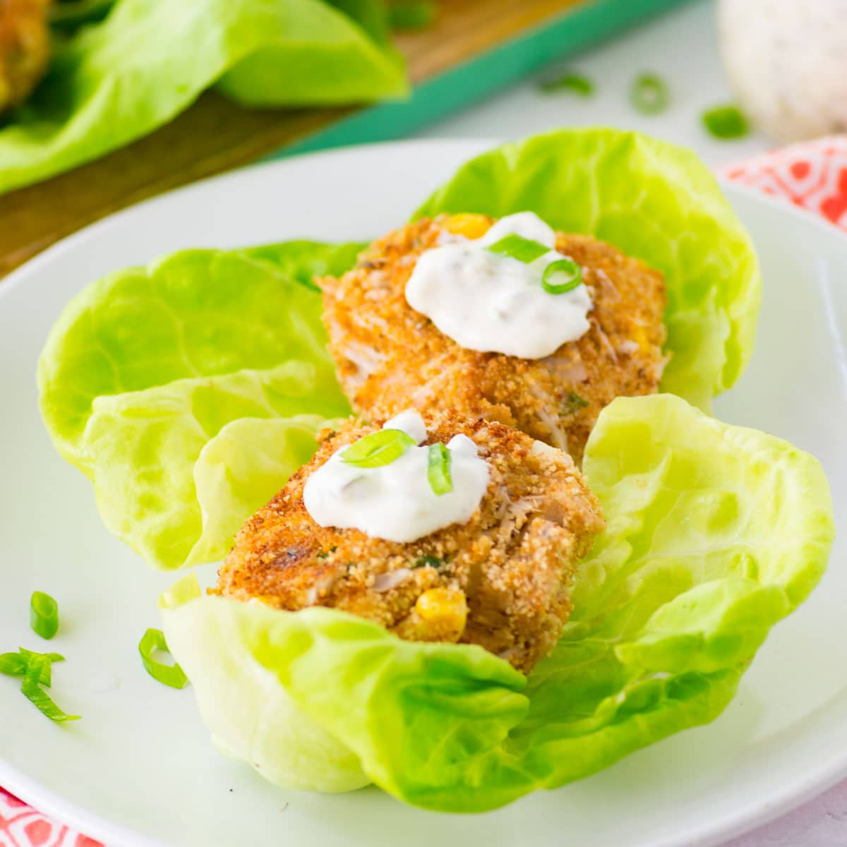 vegan crab cakes with tartar sauce and green onions on butter lettuce on white plate