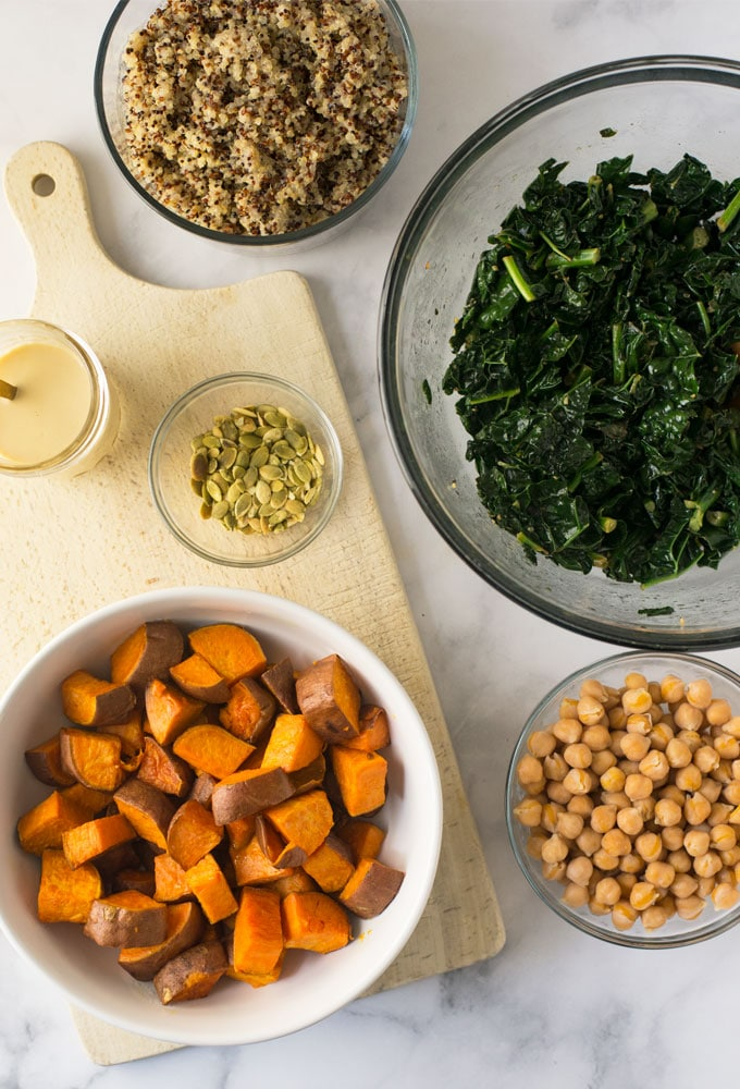 sweet potatoes, kale, quinoa, chickpeas, pepitas, and dressing on marble background