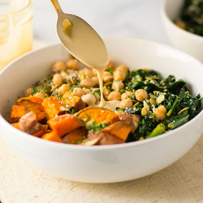 gold spoon pouring dressing on quinoa bowl with chickpeas, sweet potato, and kale