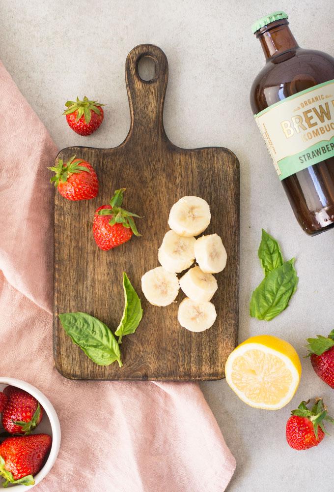 ingredients for strawberry basil kombucha smoothie on grey background