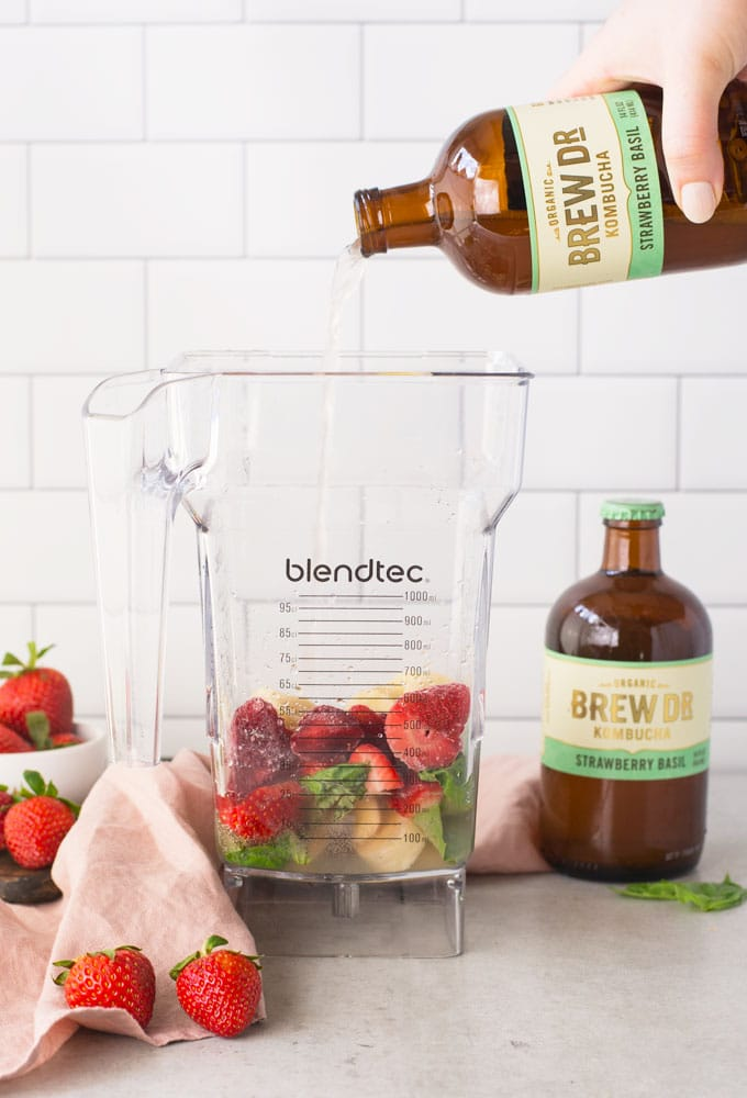 hand pouring kombucha into blender to make smoothie. Strawberries, banana, and lemon juice is in the blender