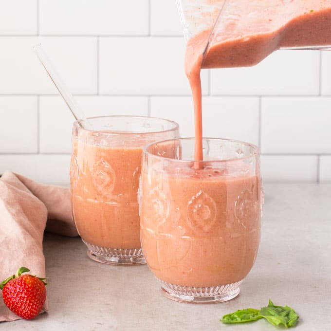 hand pouring strawberry basil kombucha smoothie from blender into glass