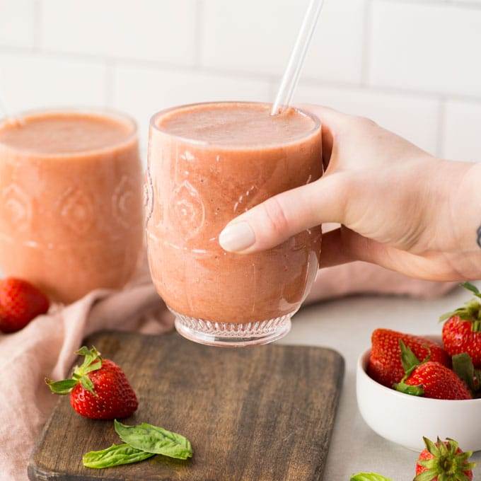 hand reaching for a strawberry smoothie with basil. there are strawberries and basil leaves in the background.