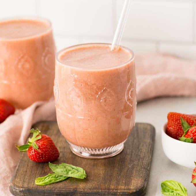 strawberry basil kombucha smoothie on wood board with pink napkin