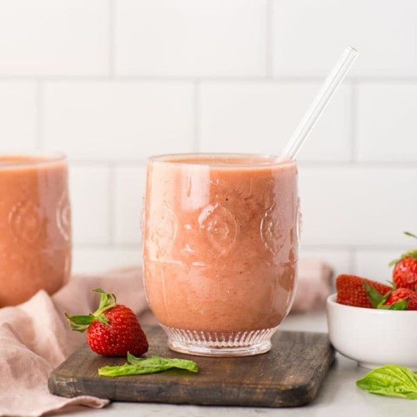 vegan strawberry basil kombucha smoothie in a glass on a white background