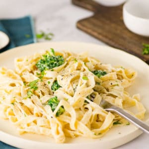 plate of vegan fettuccine alfredo with broccoli on white plate