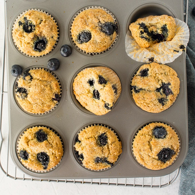 vegan and gluten free muffins in muffin pan on cooling rack.