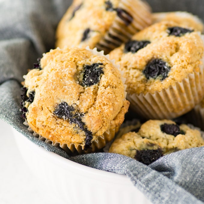 vegan and gf blueberry muffins in basket. muffins have sugar on top.