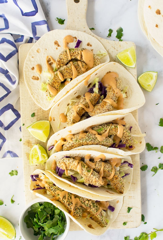 vegan avocado tacos on board with lime, flour tortillas, and chipotle sauce