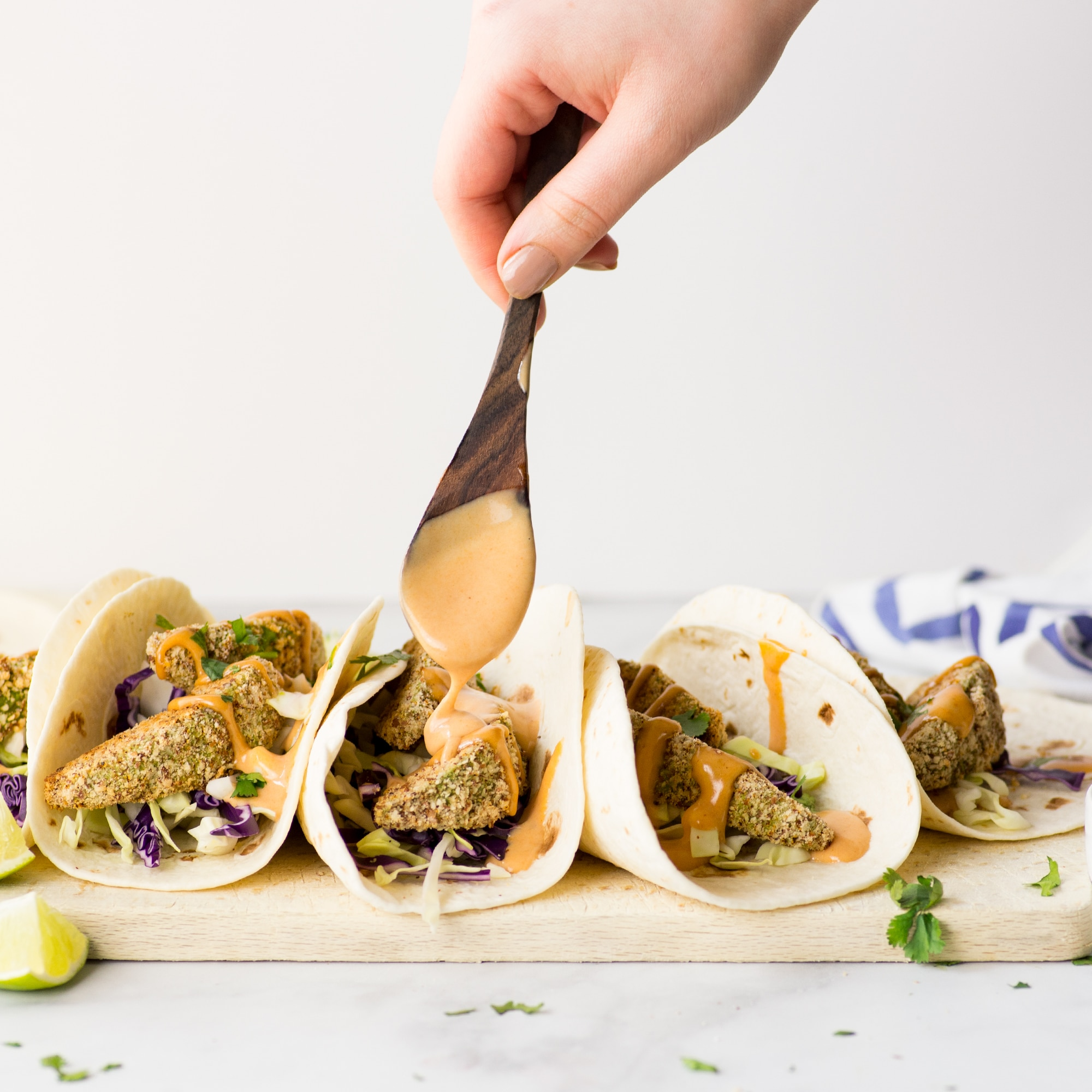 hand spooning chipotle sauce over vegan avocado tacos