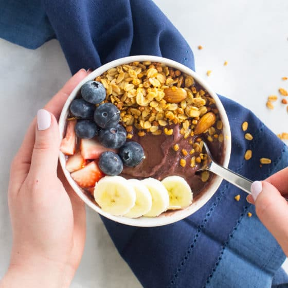 acai bowl with strawberries, blueberries, banana, granola, and honey
