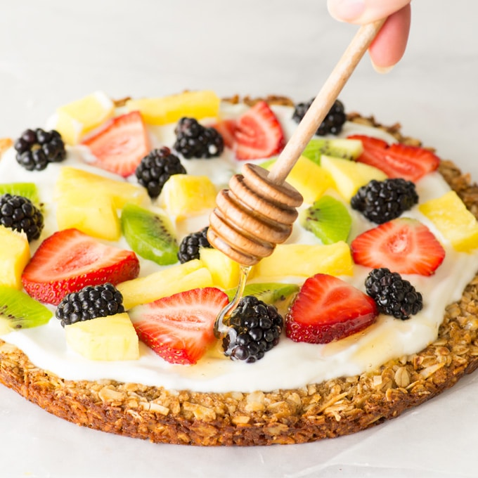 hand putting honey on healthy fruit pizza