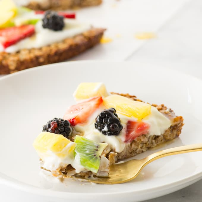 healthy fruit pizza with granola crust on plate with fresh fruit