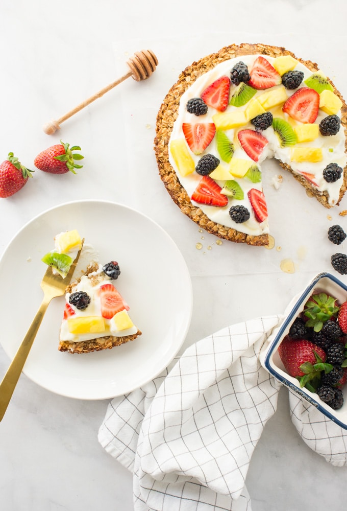 healthy fruit pizza with granola crust on white background