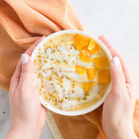 vegan orange and cream smoothie bowl with orange slices, bee pollen, and coconut flakes