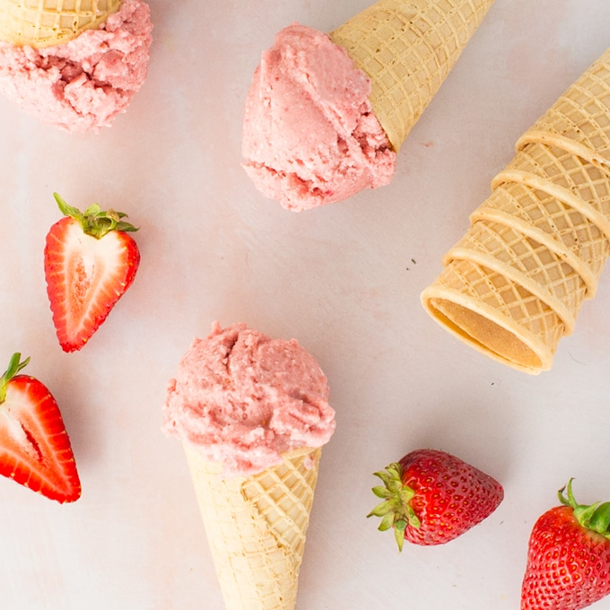 vegan strawberry banana nice cream with ice cream cones and strawberries