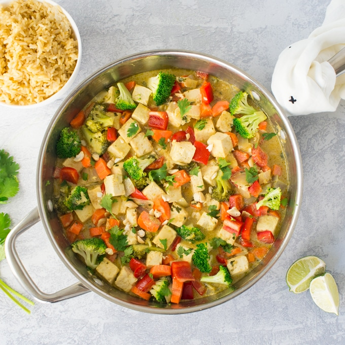 skillet of vegan thai green curry with veggies and tofu and brown rice