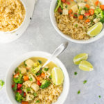 vegan thai green curry with tofu and veggies and brown rice on grey background