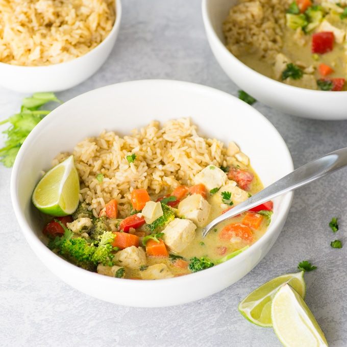vegan thai green curry in bowl with brown rice, veggies, tofu, and lime