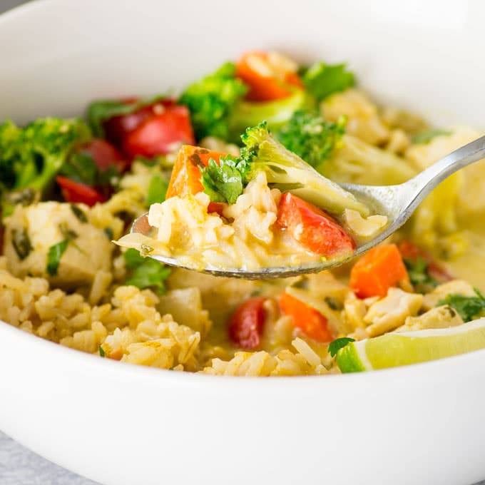 hand holding spoon of vegan thai green curry with brown rice, veggies, and tofu