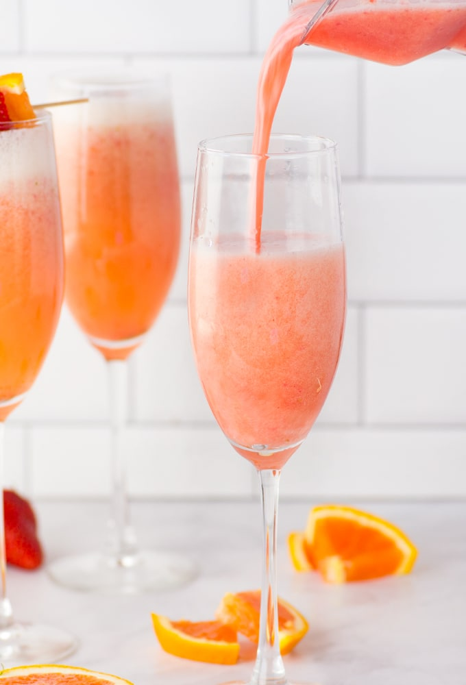 hand pouring juice into champagne flute for mimosa recipe