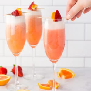 hand garnishing mimosas with strawberry and orange
