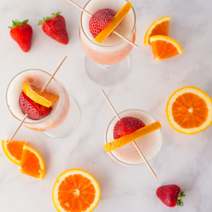 orange strawberry mimosas on marble background