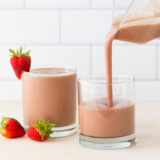 pouring smoothie into glass with strawberries